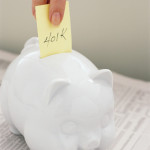 "Hand Putting Note Reading ""401K"" into Piggy Bank --- Image by © Royalty-Free/Corbis"