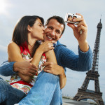 Couple Using Digital Camera in Front of Eiffel Tower